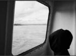 Enfant encapuchonné contemplant la mer à travers un hublot